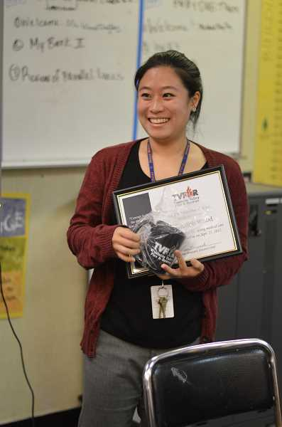 SPOKESMAN PHOTO: CLARA HOWELL - Teacher Meredith Wood receives a certificate of appreciation and a mug from Tualitin Valley Fire and Rescue after saving a student using the Heimlich maneuver.