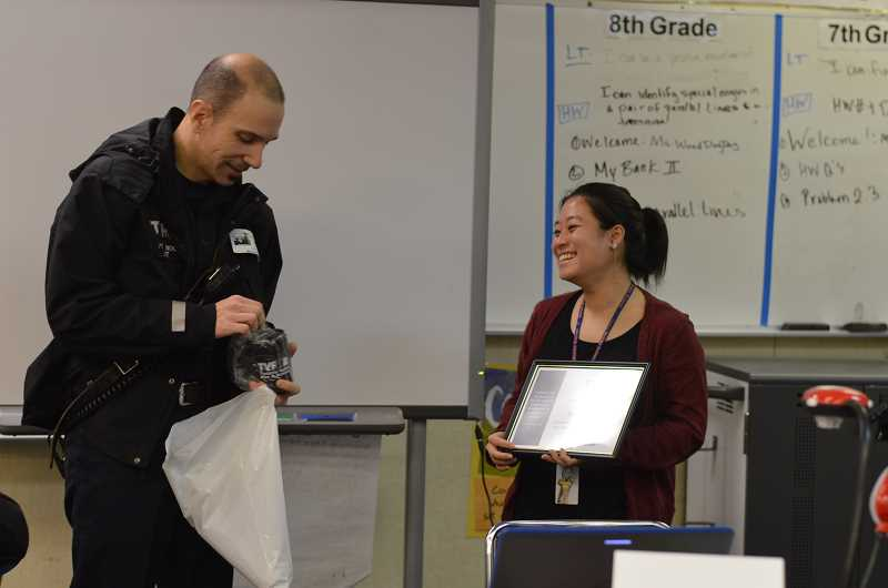 SPOKESMAN PHOTO: CLARA HOWELL - Tualatin Valley Fire and Rescue Captain Tim Nokes presents teacher Meredith Wood with tokens of honor in front of her math class.