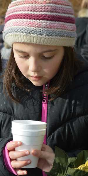 SPOKESMAN PHOTO: CLARA HOWELL  - Louisa Sneath, 8, marvels at the fry swimming around in the cup.
