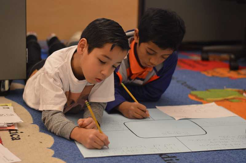 SPOKESMAN PHOTO: CLARA HOWELL - Third-graders Adan Vasquez (left) and Efty Otto (right) work on a class assignment, learning about one particular stage of the salmon's life cycle.
