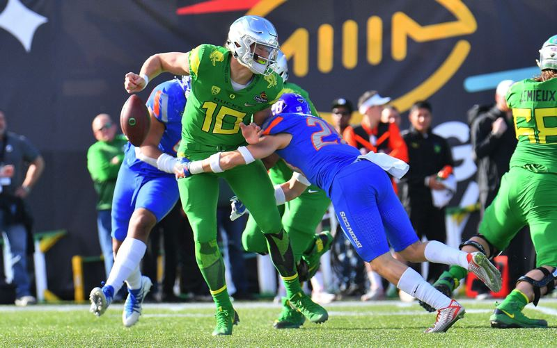 TRIBUNE PHOTO: SAM WASSON - Oregon Ducks quarterback Justin Herbert fumbles the ball after he is hit by Boise State Broncos safety Kekaula Kaniho  during the 26th Las Vegas Bowl at Sam Boyd Stadium.