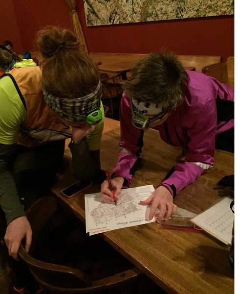 COURTESY PHOTO - Participants analyze a map during the annual Multnomah Village Night-O orienteering event.