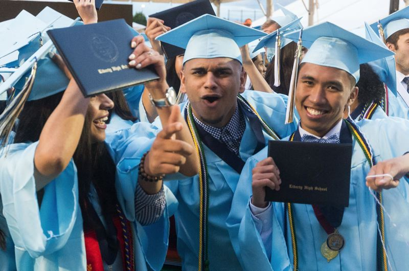 CHRISTOPHER OERTELL/HILLSBORO TRIBUNE - Liberty High School students show off their diplomas during a graduation ceremony at Hillsboro Stadium June 10, 2017.