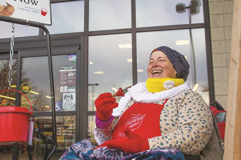 INDEPENDENT PHOTO: JULIA COMNES - Dina Miller, a bell ringer for the Salvation Army, sings Christmas carols while at her post at the Woodburn Safeway. She hopes her music brings joy to shoppers while helping her raise money for a good cause.