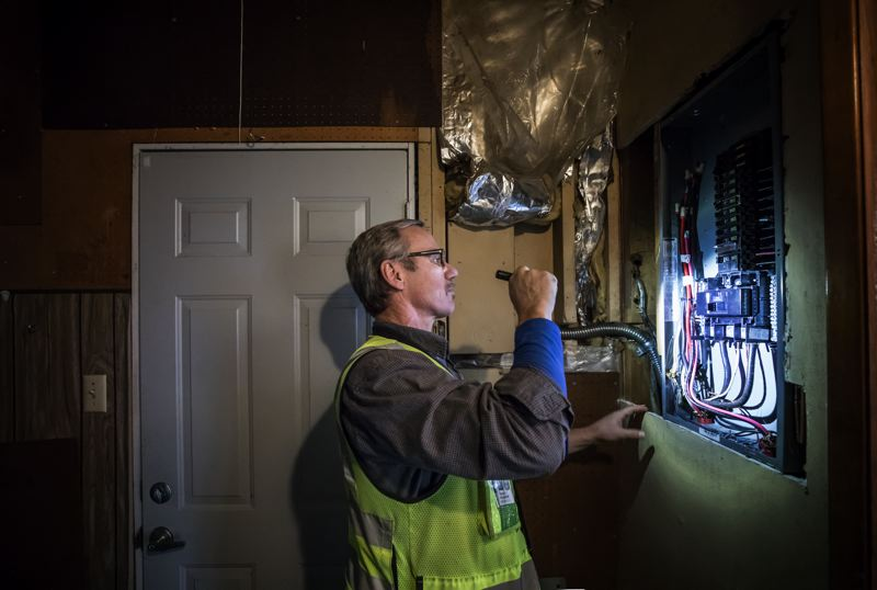 PAMPLIN MEDIA GROUP: JONATHAN HOUSE - Dave Scranton, senior electrical inspector for the City of Portland, inspects a newly installed electrical panel during a home visit.