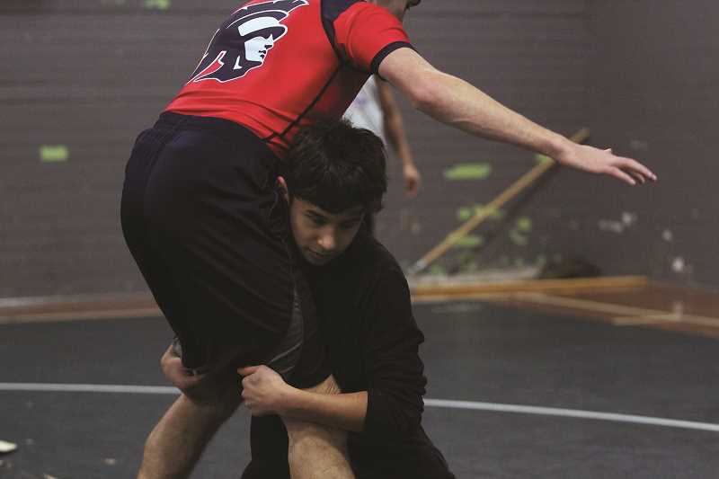 PHIL HAWKINS - Kennedy's Mateo Marrow practices against head coach Dewey Enos on Thursday. Marrow became the first Trojan wrestler to win a bracket championship this season after going undefeated at the Bill Hagerty Invitational in Nestucca on Saturday.