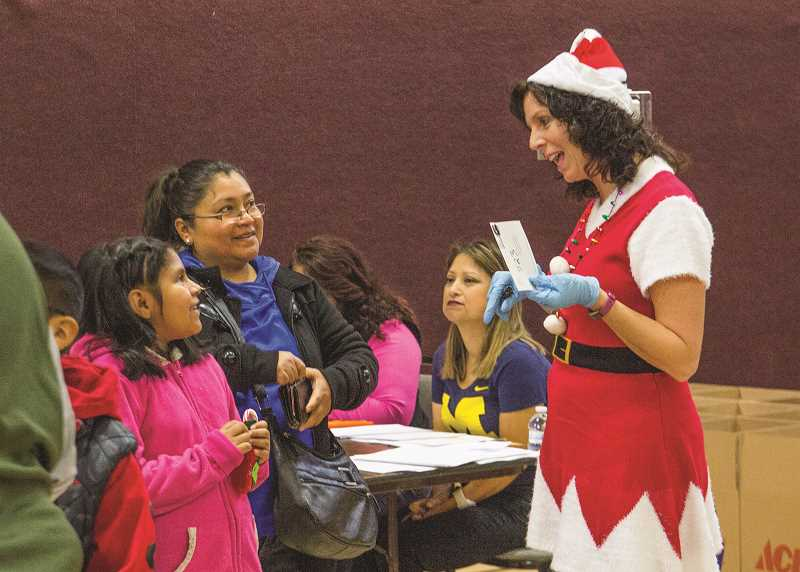 INDEPENDENT PHOTO: JULIA COMNES - Volunteer Gina Audritsh chats with attendees of the Dec. 16 distribution day.