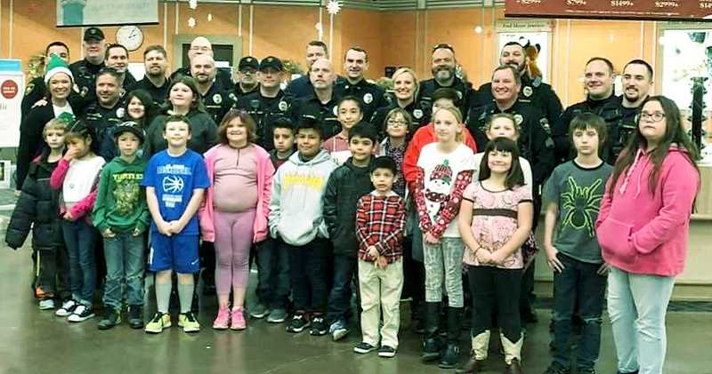 SUBMITTED PHOTO - Newberg-Dundee Police Department officers pose with children who participated in the Shop with a Cop program to purchase gifts for family members at Fred Meyer.