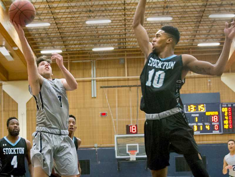 SUBMITTED PHOTO - Thomas Rico lifts a floater over a Stockton defender during George Fox's 74-62 home loss to Stockton Sunday at Miller Gymnasium.