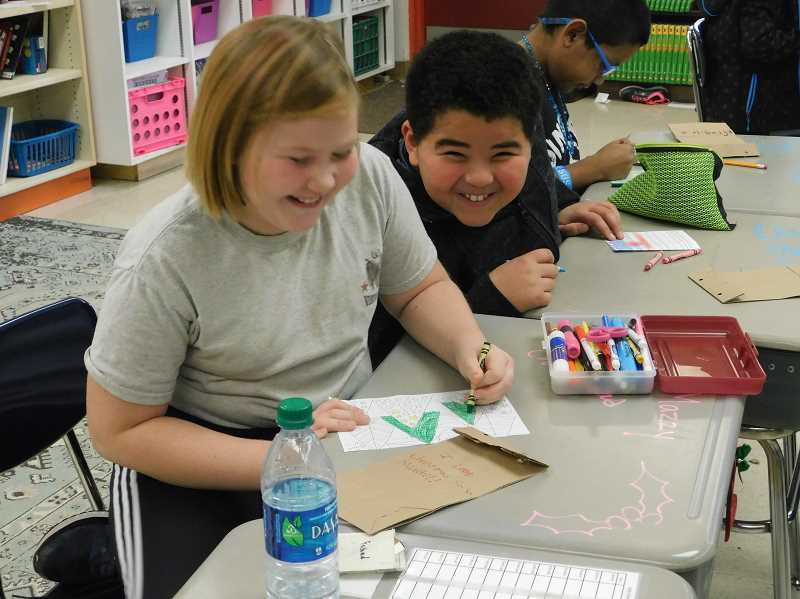 ESTACADA NEWS PHOTO: EMILY LINDSTRAND - Students in Hillary Tidds fourth grade class at River Mill Elementary School are all smiles as they work on Christmas cards and elf applications during Frederick the elfs visit to their class.
