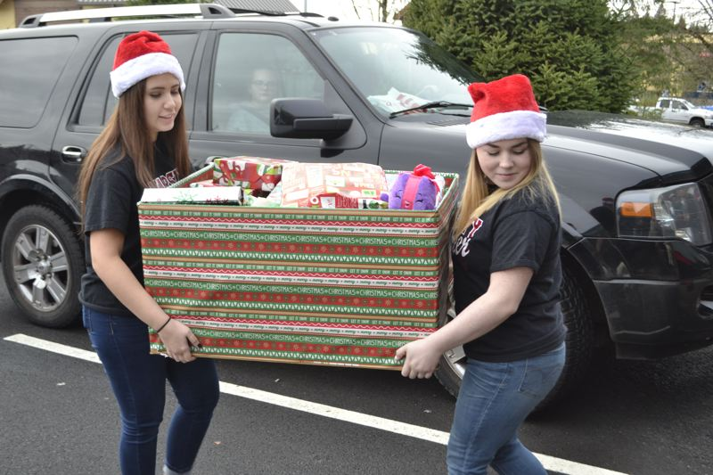 POST PHOTO: BRITTANY ALLEN - Sandy High School cheerleaders helped serve food and act as Santa's helpers at Jackson Clark's Christmas party for struggling families on Sunday, Dec. 17.