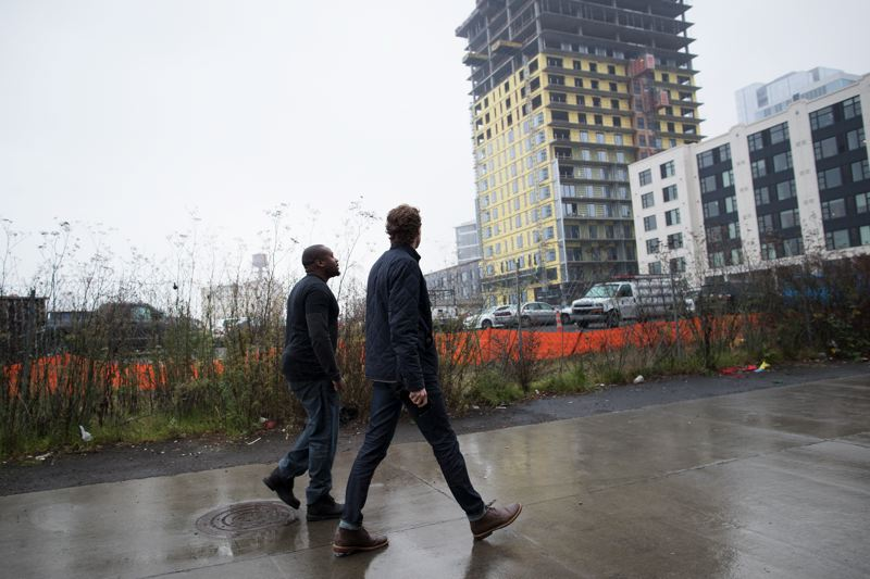PAMPLIN MEDIA GROUP: JAIME VALDEZ - Tyler Peterson and Tyrone Poole of OneAppOregon take a stroll past the upcoming Block 17 apartment building in the Pearl. Their app was designed originally for moderate to low income tenants and has been backed by Portlands Housing Bureau, but it could work for any property management company that signs up.
