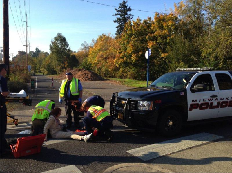 PAMPLIN MEDIA GROUP FILE PHOTOS - Clackamas Fire personnel attend to Gillian Hibbs, 70, after a Milwaukie police officer hit her while she biked across a marked crosswalk on the Springwater Corridor.