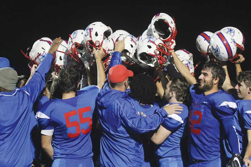 WILL DENNER/MADRAS PIONEER - Madras football players and coaches huddle after the White Buffalos beat Valley Catholic Sept. 15, and snapped a 23-game losing streak dating back to 2014. Scroll down to see where Madras football ranked on the Pioneer's countdown.