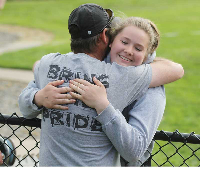 WILL DENNER/MADRAS PIONEER - Catylynn Duff (right) hugs Culver track and field head coach Mike Dove moments after she won the 2A girls discus state title and set a new record last May in Eugene.