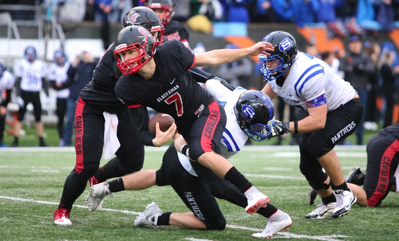REVIEW/NEWS PHOTO: JIM BESEDA - Clackamas quarterback Mitchell Modjeski takes the ball to the South Medford 20-yard line, setting up Jeffrey Nelson's game-winning 37-yard field in the 6A state championship game.