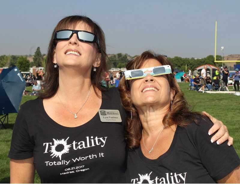 HOLLY M. GILL - Lysa Vattimo, solar eclipse event coordinator for the city of Madras, and her sister, Susan Duff, of Scott City, Kansas, take in the eclipse in the Madras High School football stadium, where visitors from around the globe gathered.