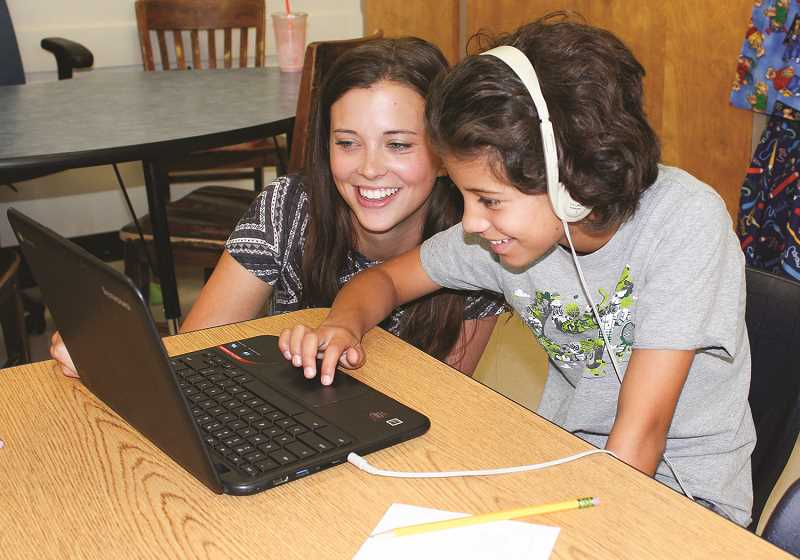CENTRAL OREGONIAN - Classroom certified aid Channing Loveday, left, helps student Tatum Holliday with a lesson on a Chromebook during Kiwanis Summer School last July. The service organization has offered to support a fifth year of summer school.