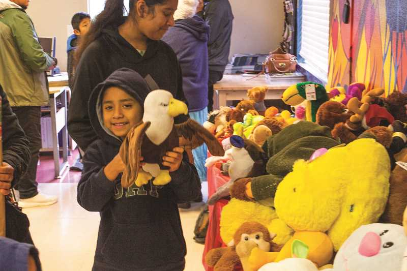 INDEPENDENT PHOTO: JULIA COMNES - An attendee of the distribution day makes a selection from the pile of donated toys.