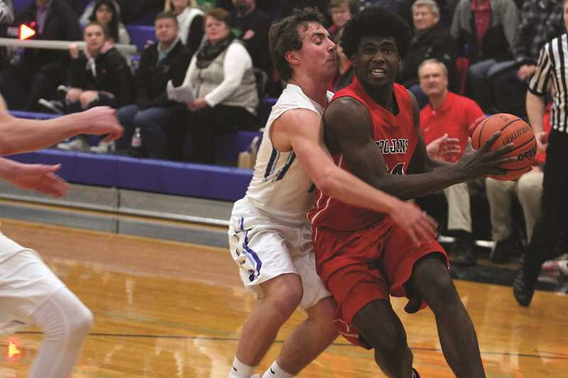 PHIL HAWKINS - Kennedy's Emorej Lynk absorbs contact from St. Paul's Justin Herberger on his way to the rim in the Trojans' victory over the Bucks last week.