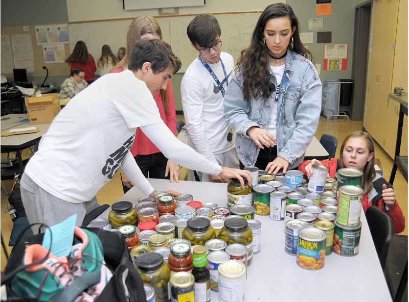 SETH GORDON - Associated Student Body students from Newberg High School collect food donations during the Rex Hill Rivalry contest.