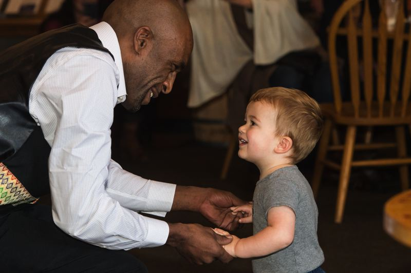 NEWS-TIMES FILE PHOTO: CHRISTOPHER OERTELL - Samson Beriso dances with 1-year-old Jace McRobert during an Ethiopian coffee ceremony at BJ's Coffee Co. in Forest Grove in November.