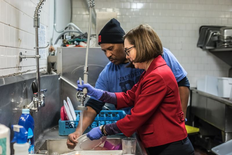 PORTLAND TRIBUNE: JONATHAN HOUSE - Larry Jones, of the Human Solutions Family Center in Portland, shows Gov. Kate Brown around the kitchen during a tour and press conference.