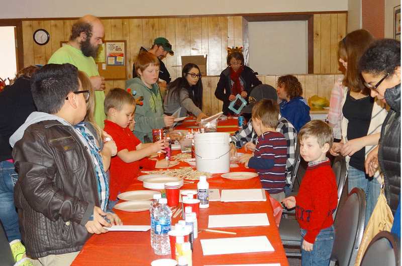PHOTO BY GRETCHEN SCHLIE - Volunteers help children work on crafts at the LINC Christmas party.