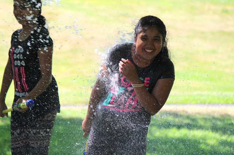 SPOKESMAN FILE PHOTO - Vindhya Adamala gets drenched by a blast of water during a water fight in Murase Plaza park during the end of summer party for participants in the teen reading program for Wilsonville Library.