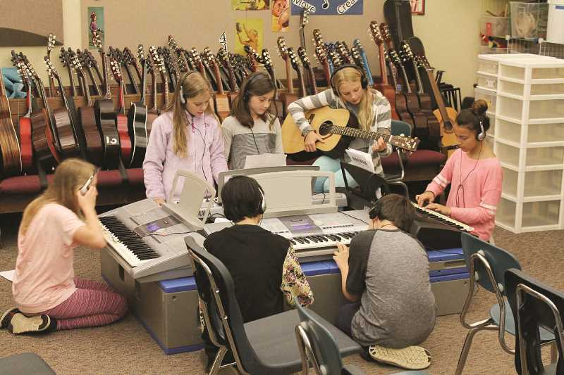 SPOKESMAN FILE PHOTOS - Boones Ferry fifth-graders fine tune their songs before performing in front of the class after working with an in-residence professional musician for two weeks in June.