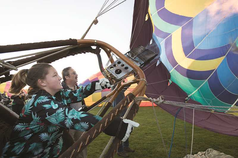 TIMES FILE PHOTO - Grace Ingram controls the burners as she brings up the Firenze balloon, owned by her grandfather Koi Murai, during the Tigard Festival of Balloons at Cook Park. Ingram is training to become a pilot for her high school senior project.