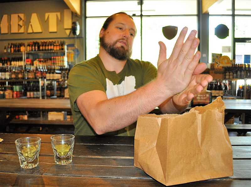 "TIMES FILE PHOTO - Tyler Staples does a ""hop rub"" of a Cascade hop at Uptown Market. The oils left on his hand smelled like earth and grapefruit."
