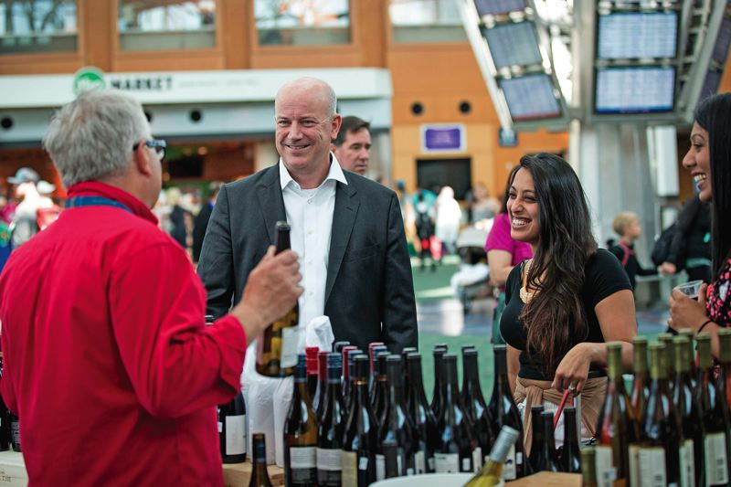 PAMPLIN MEDIA GROUP: JAIME VALDEZ - Port of Portland Director Curtis Robinhold schmmozes with wine vendors on one of his strolls through the Portland International Airport.