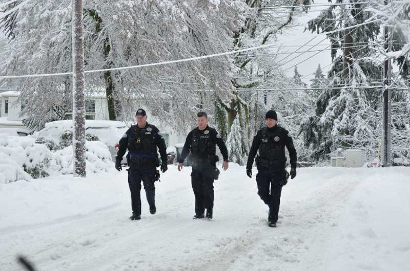SUBMITTED PHOTO: LAKE OSWEGO POLICE DEPARTMENT - LOPD Lt. Doug Treat (from left), Officer Drew Boggs and Officer Bryan Sheldon return on foot from a call for help during January's brutal winter snowstorm. By the end of the week, the city's first responders had handled more than 300 storm-related incidents.