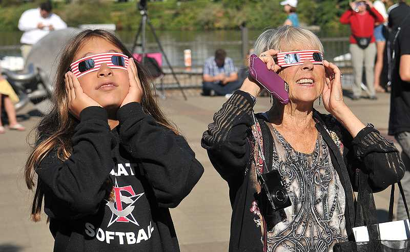 REVIEW PHOTO: VERN UYETAKE - Ten-year-old Sarah Greenspan (left) and Annie Arkebauer look skyward in August as they wait for the total solar eclipse to pass over Sundeleaf Plaza in Lake Oswego, where hundreds gathered for the unique event.