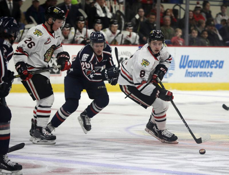 TRIBUNE PHOTO: JONATHAN HOUSE - Cody Glass (right) of the Portland Winterhawks wheels around the Tri-City defense.