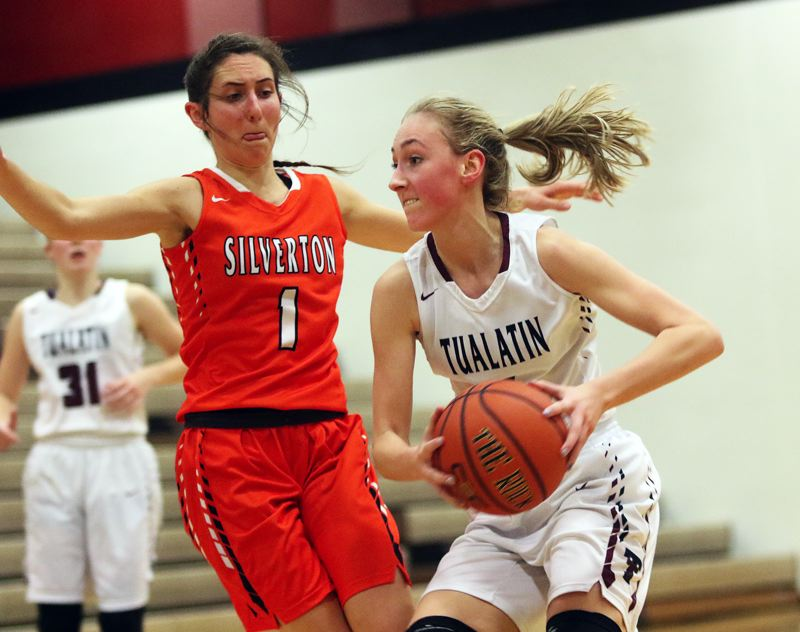 DAN BROOD - Tualatin High School junior Natali Denning (right) looks to drive past Silverton's Jori Paradis during last week's non-league game. The Timberwolves scored a 43-39 victory.
