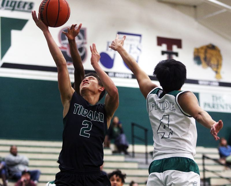DAN BROOD - Tigard junior Jazz Ross (left) goes up to the basket during the victory over Parkrose.