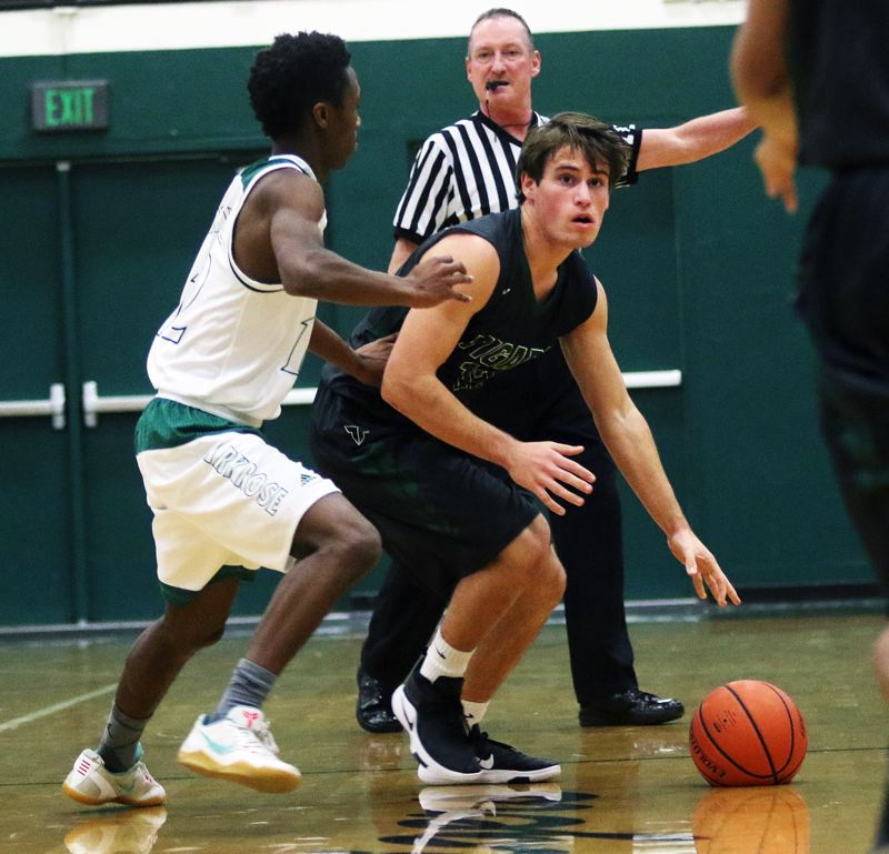 DAN BROOD - Tigard junior Carson Crist (right) brings the ball up court during the win over Parkrose.
