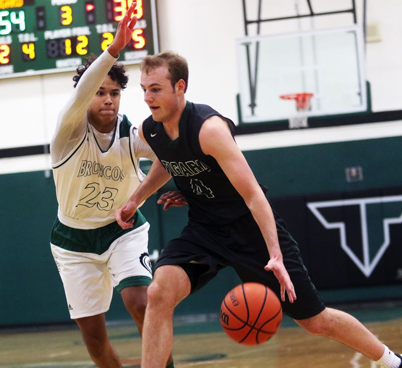 DAN BROOD - Tigard junior Stevie Schlabach (right) drives against Parkrose's Tre Anderson.