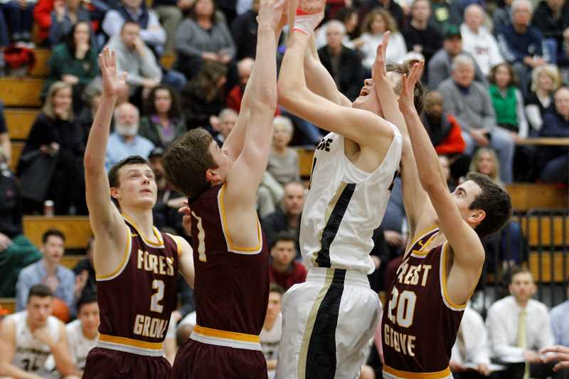 NEWS-TIMES PHOTO: WADE EVANSON - Viking basketball players Bailey Evers (2), Dillon James (1), and Kyle Thompson (20) swarm a Southridge defender during Forest Grove's playoff game last winter.