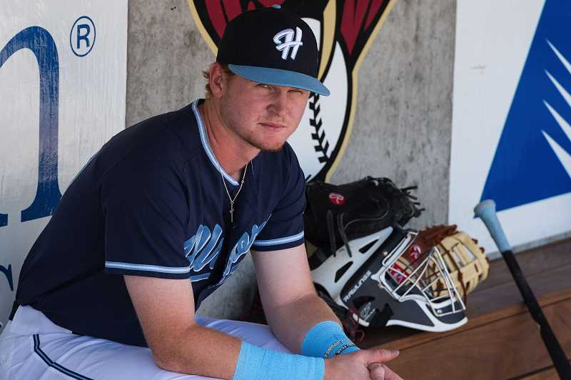 HILLSBORO TRIBUNE PHOTO: CHRISTOPHER OERTELL - Hillsboro Hops first baseman Pavin Smith sits in the dugout between innings during a Hops game last August. Smith surprised his parents Christmas morning buying paying their mortgage on their home.