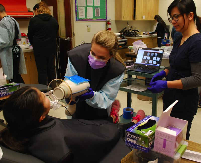 COURTESY - Virginia Garcia dental hygienist Kristina Petersen uses a portable X-ray machine to capture images of a student's teeth at Echo Shaw Elementary School in Cornelius. To her right is Cathy Dang, School Based Health Center dental coordinator.