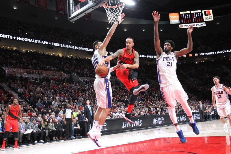 TRIBUNE PHOTO: JAIME VALDEZ - Trail Blazers point guard Shabazz Napier dishes the ball to a 3-point shooter after drawing two Philadelphia defenders during Thursday night's Portland victory at home over the 76ers.