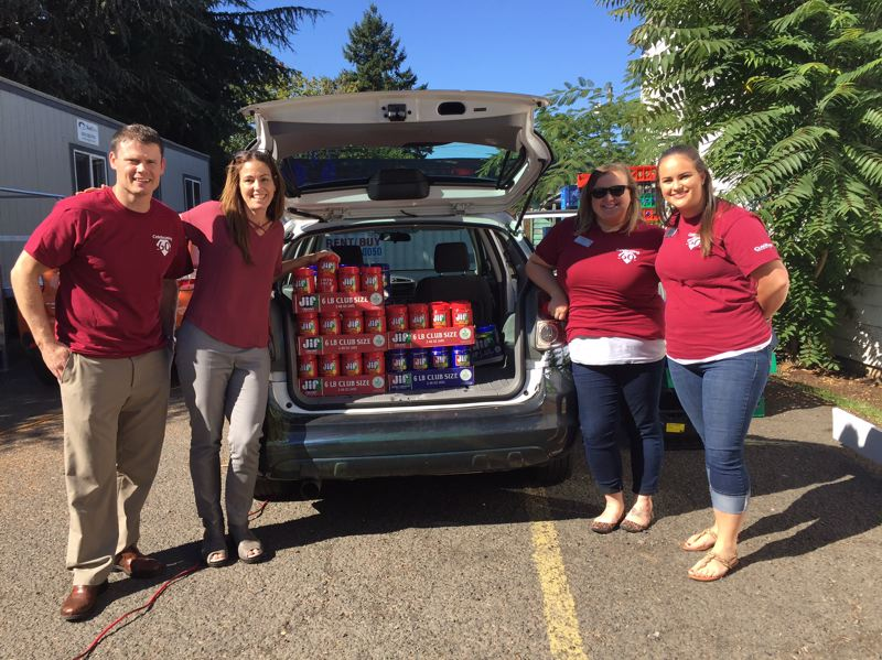 PHOTO COURTESY: CFCU - Clackamas Federal Credit Union VP of Member Service Luke McMurray (from left) drops off a donation of peanut butter to Debra Mason, Clackamas Service Center executive director, joined by CFCU Marketing Specialist Hilary Kissell and CFCU Marketing Team Lead Meagan Rice.