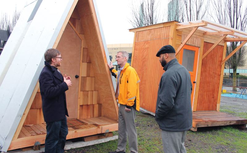 PORTLAND TRIBUNE: LYNDSEY HEWITT - Mayor Ted Wheeler talks to Todd Perry of Portland State University's Center for Public Interest Design outside some of the small shelters that were later moved to Kenton for homeless women.