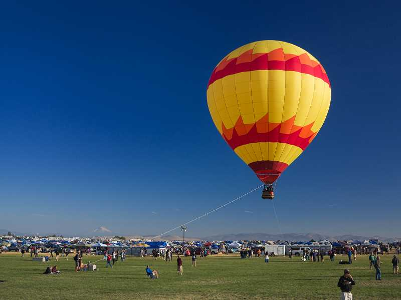 DAVID BROWNELL - A hot air balloon lifts off from SolarTown, north of Madras, on the day of the eclipse, Aug. 21, 2017.