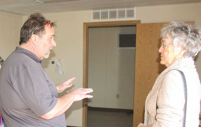 CENTRAL OREGONIAN - Greg Sanders, executive director of Redemption House Ministries, a faith-based nonprofit serving the homeless, talks to Prineville Mayor Betty Roppe at a grand opening for a new local men's shelter.