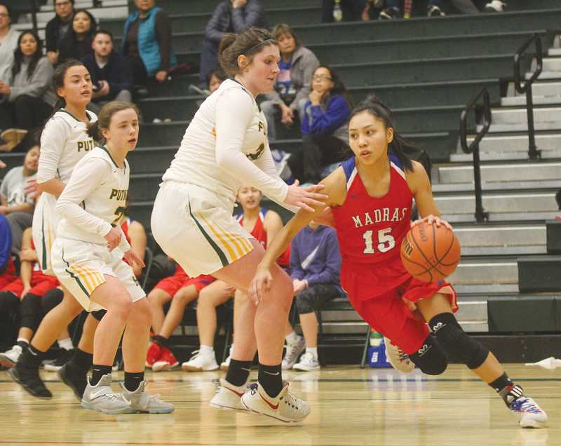 WILL DENNER/MADRAS PIONEER - Madras wrapped up the Les Schwab Oregon Holiday Hoops Fest with a 57-38 win over Putnam last Saturday. Above, Lynden Harry (15) slashes toward the basket as Putnam defenders look on.