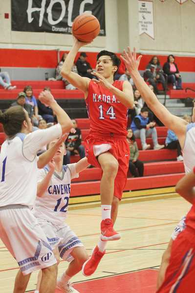 WILL DENNER/MADRAS PIONEER - Byron Patt (14) attacks the hoop during the first half against Grants Pass on Saturday.